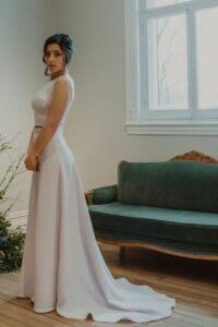 Robe minimaliste tout en crêpe de satin près du corps, elle souligne les formes avec grâce.
